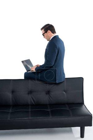 Geschäftsmann mittleren Alters sitzt auf der Couch und benutzt Laptop auf weiß
