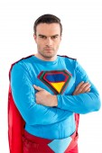 confident handsome superman standing with crossed arms and looking at camera isolated on white
