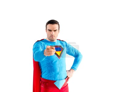 confident male superhero standing with hand on waist and pointing at camera isolated on white