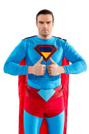 handsome male superhero showing thumbs up and looking at camera isolated on white