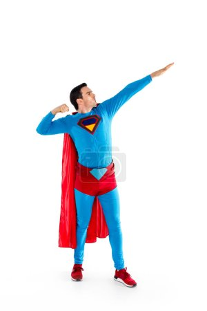 full length view of handsome man in superhero costume looking away isolated on white