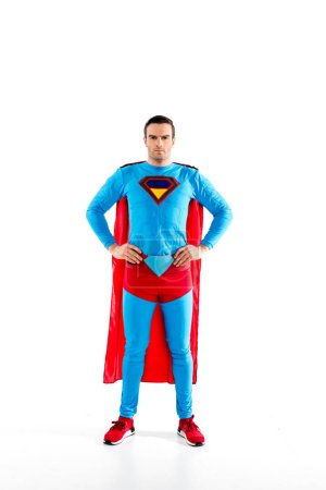 full length view of handsome mid adult superman standing with hands on waist and looking at camera isolated on white