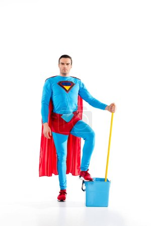 confident man in superhero costume standing with mop and bucket, looking at camera on white