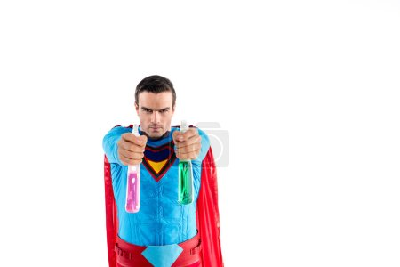 superman holding plastic spray bottles with cleaning liquid and looking at camera isolated on white