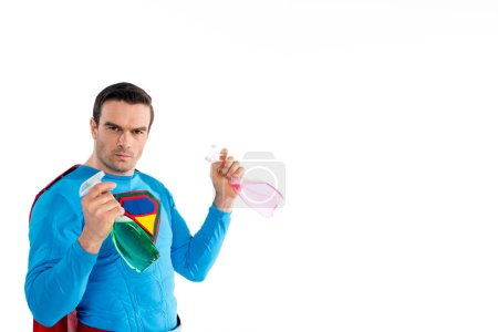 confident superhero holding plastic spray bottles with cleaning liquid and looking at camera  isolated on white