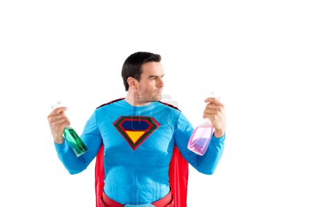 handsome superhero holding plastic spray bottles with cleaning liquid isolated on white