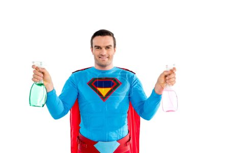 Photo for Handsome man in superhero costume holding spray bottles and smiling at camera isolated on white - Royalty Free Image
