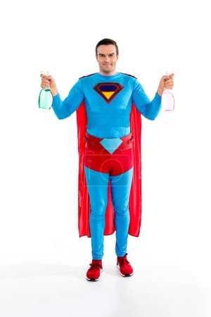 handsome superman holding spray bottles and smiling at camera isolated on white