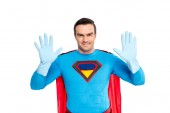 handsome superhero showing hands in rubber gloves and smiling at camera isolated on white