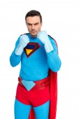 serious male superhero in rubber gloves standing with fighting position and looking at camera isolated on white