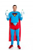 handsome man in superhero costume holding bottles with detergent and smiling at camera isolated on white