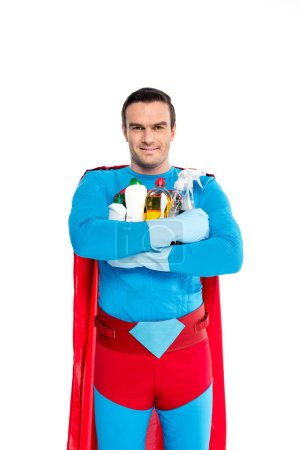 superman in rubber gloves holding cleaning items and smiling at camera isolated on white