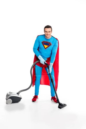 superman in rubber gloves using vacuum cleaner and smiling at camera on white