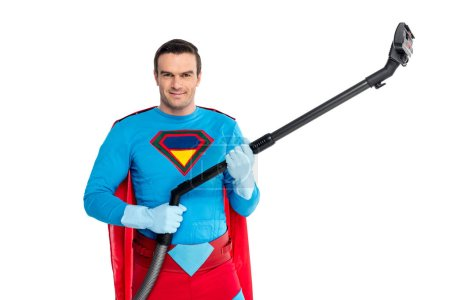 handsome man in superhero costume holding vacuum cleaner and smiling at camera isolated on white