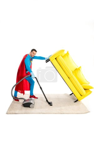 male superhero holding couch while cleaning carpet with vacuum cleaner and looking at camera isolated on white