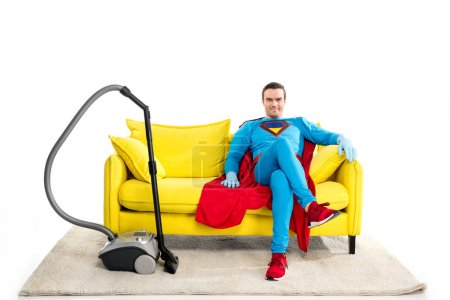 smiling male superhero in rubber gloves sitting on sofa near vacuum cleaner and looking at camera isolated on white