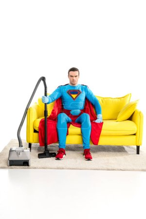 superman with vacuum cleaner sitting on couch and looking at camera on white