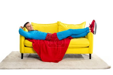 superman lying on couch and smiling at camera isolated on white