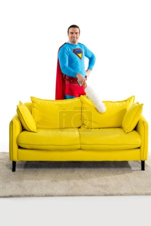 handsome man in superhero costume cleaning couch with duster and smiling at camera on white