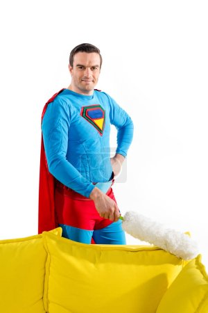 handsome male superhero cleaning couch with duster and smiling at camera isolated on white