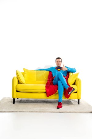 handsome male superhero sitting on couch and showing thumb up on white