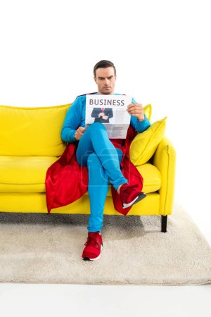 full length view of serious male superhero sitting on couch and reading business newspaper isolated on white