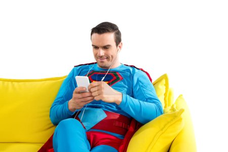 smiling superman in earphones sitting on sofa and using smartphone isolated on white