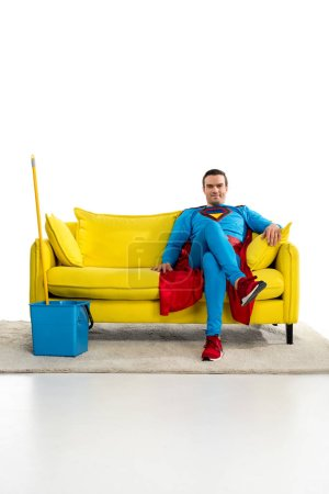 smiling male superhero sitting on couch near bucket and mop on white