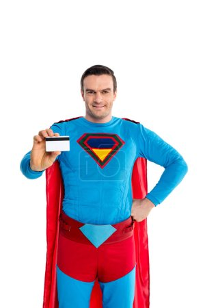 handsome man in superhero costume holding credit card and smiling at camera isolated on white