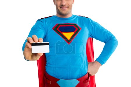 cropped shot of smiling male superhero holding credit card isolated on white