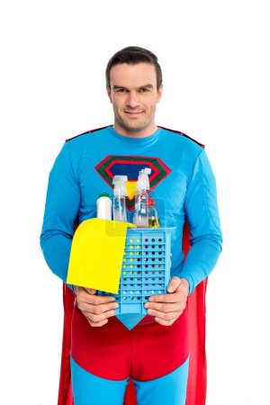 handsome man in superhero costume holding cleaning supplies and smiling at camera isolated on white