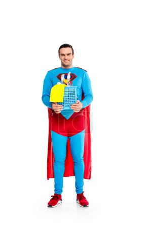 handsome male superhero holding cleaning supplies and smiling at camera isolated on white