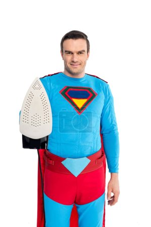 handsome man in superhero costume holding iron and smiling at camera isolated on white