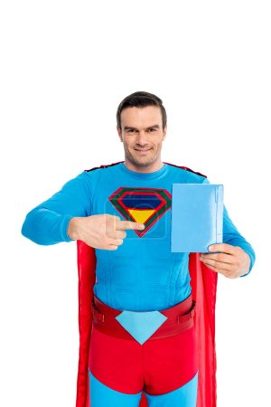 handsome superman pointing with finger at blank box with soap powder and smiling at camera  isolated on white