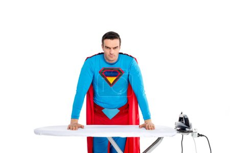 handsome male superhero leaning at ironing board and looking at camera isolated on white
