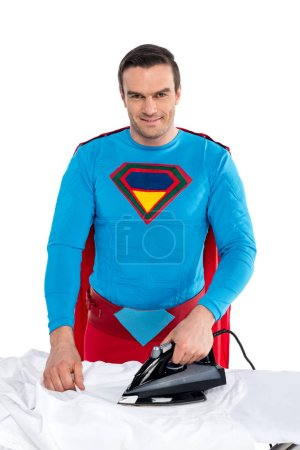Photo for Handsome man in superhero costume ironing clothes and smiling at camera isolated on white - Royalty Free Image