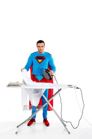 man in superhero costume ironing clothes and looking at camera on white