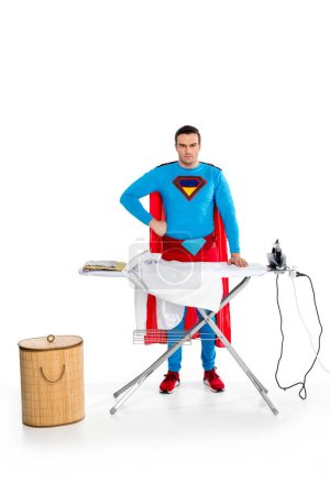 handsome superman ironing clothes and looking at camera on white