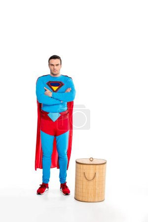 handsome male superhero standing with crossed arms near laundry basket and looking at camera isolated on white