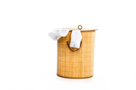 wicker laundry basket with clothes isolated on white
