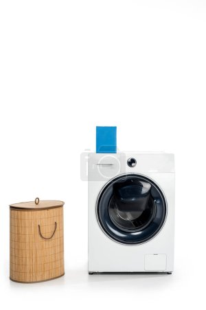 blank box with soap powder on washing machine and laundry basket isolated on white