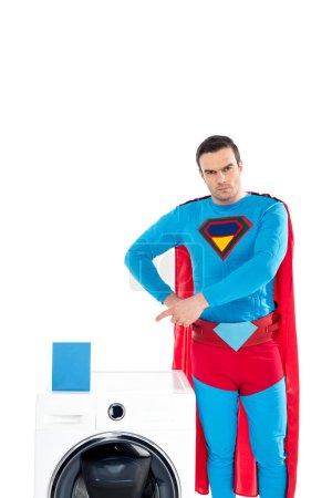 handsome superhero pointing with finger at washing machine and soap powder isolated on white
