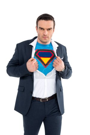 businessman showing superhero costume under suit and looking at camera isolated on white
