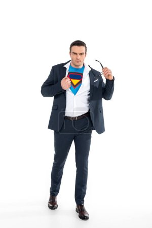 confident businessman in superhero costume under suit taking off eyeglasses and looking at camera isolated on white