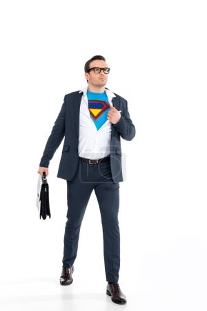 confident businessman in eyeglasses holding briefcase and wearing superhero costume under suit isolated on white