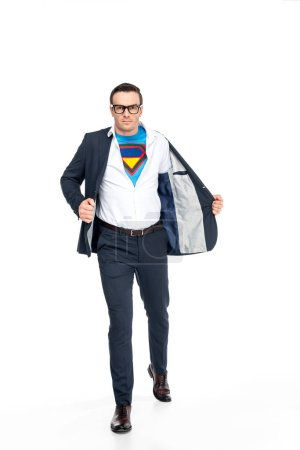 confident businessman in superhero costume under suit taking off suit jacket and looking at camera isolated on white