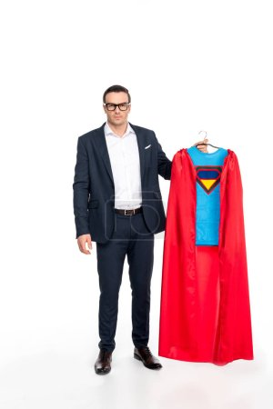 businessman in eyeglasses holding hanger with superhero costume and looking at camera isolated on white