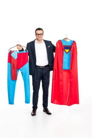 businessman in eyeglasses holding hangers with superhero costume and smiling at camera isolated on white