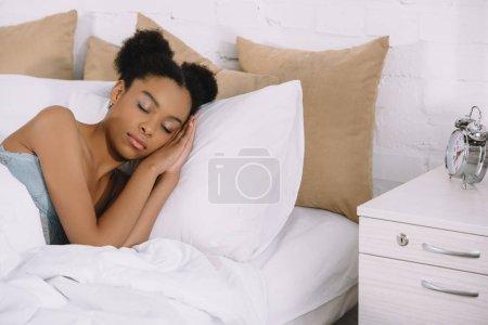 beautiful african american girl sleeping on bed with alarm clock near