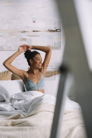 smiling african american woman stretching and waking up in bedroom in morning